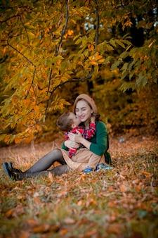 Счастливая молодая мать играть и веселиться с сыном маленький ребенок на солнечный теплый осенний день в парке.