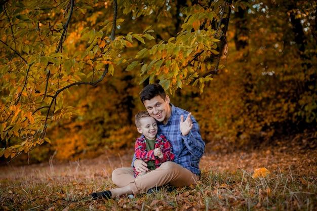 秋の公園で屋外楽しんで幸せな家族。父と息子の黄色のぼやけた葉の背景。