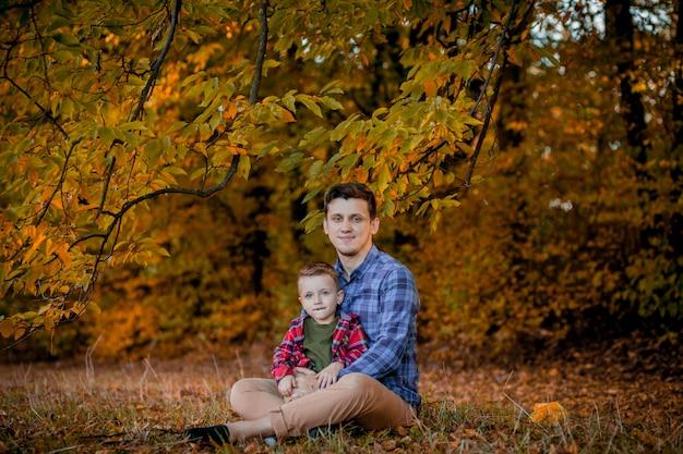 Счастливая семья весело открытый в осенний парк. отец и сын против запачканной желтым цветом предпосылки листьев.