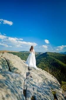 山の岩の上に座って、フィヨルドを見て、丘でハイキングのウェディングドレスの少女の裏
