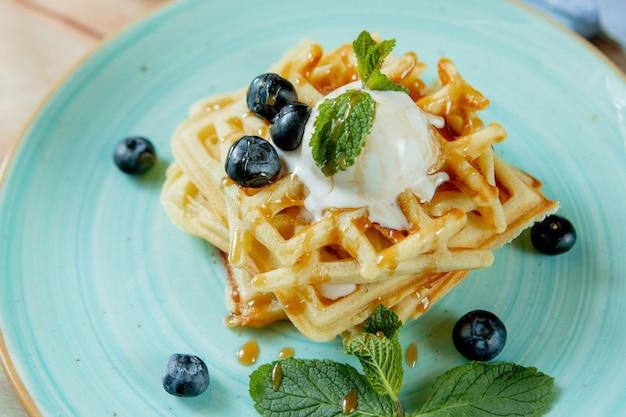 焼きたての自家製クラシックベルギーワッフルにアイスクリーム、新鮮なブルーベリー、木製の背景にミントをトッピング。朝食のコンセプト