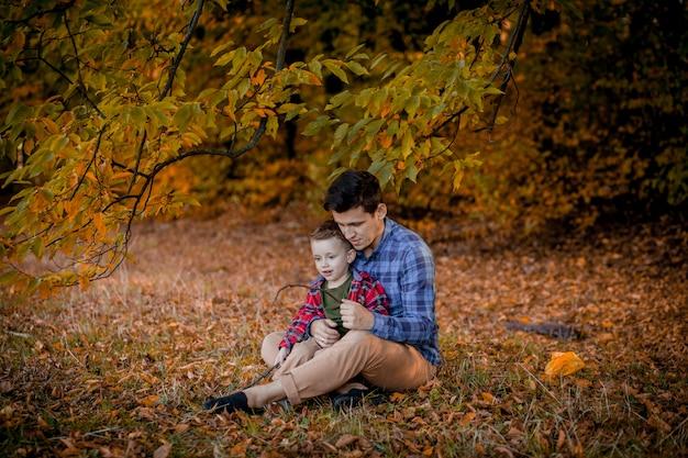 秋の公園で屋外楽しんで幸せな家族。父と息子の黄色のぼやけた葉の背景。幸せな家族の概念、父の日