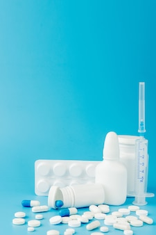 Разбросанные разнообразные таблетки, лекарства, спай, бутылки, термометр, шприц и пустая тележка для покупок