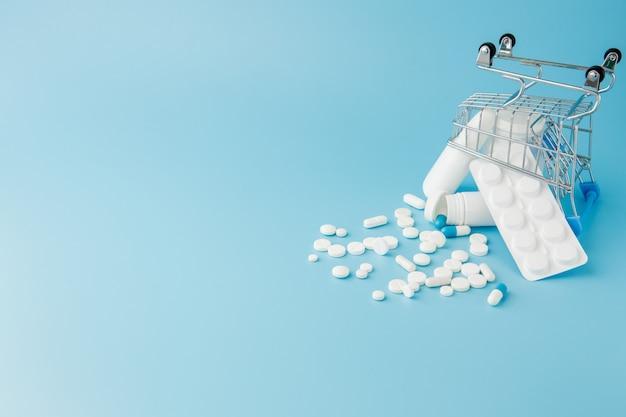 Разбросанные разнообразные таблетки, лекарства, спай, бутылки, термометр, шприц и пустая тележка для покупок. аптека торговая концепция