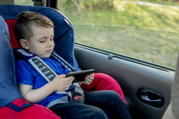 車の座席に座っている退屈な男の子の肖像画。子供の輸送の安全性。
