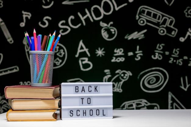 カラフルな学用品と学校の看板に戻る