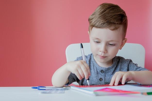 Милый мальчик дома писать с цветной карандаш