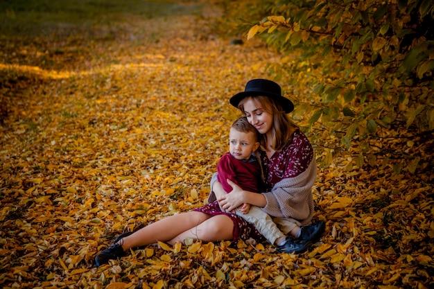 Счастливая молодая мать, играя с ребенком в осенний парк с кленовыми листьями