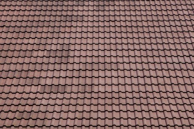 Коричневая крыша с металлической черепицей на голубом небе