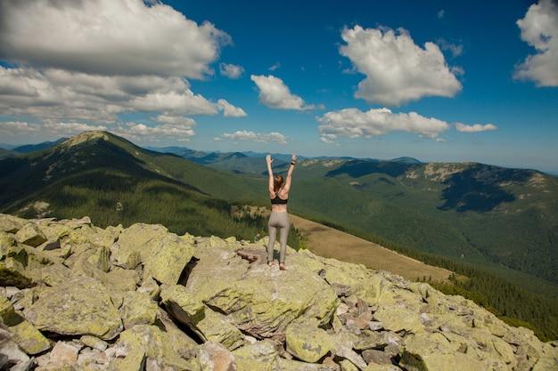 山の頂上にいる少女は手を挙げました。日の出と遠くの山の範囲で広い夏の山の景色が覆われています。自然の美しさ
