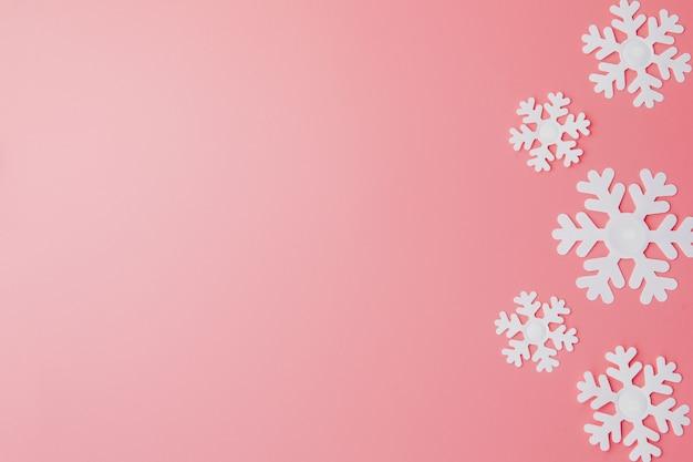 雪の結晶とピンクの冬のパターン。クリスマス。平干し。テキストのコピースペース