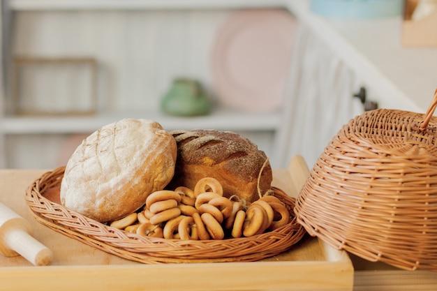 Ассортимент хлеба возле плетеной корзины на столе в деревенской кухне.