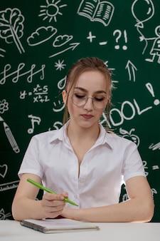 Молодой учитель сидит возле доски в классе.