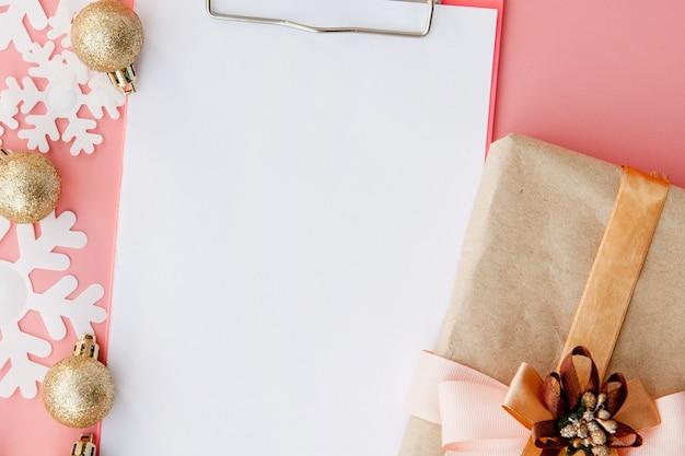 Рождественский подарок в женских руках и блокнот на розовом, вид сверху