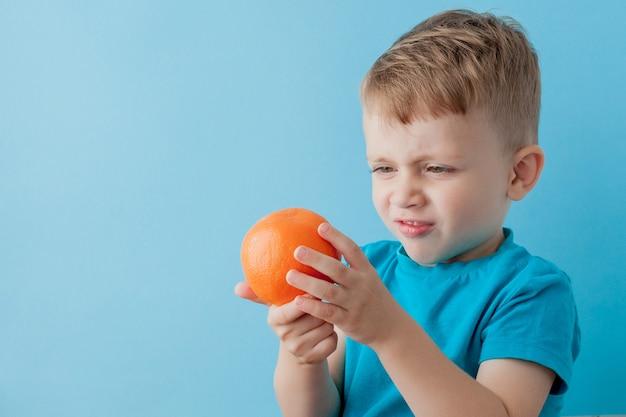 青色の背景に彼の手でオレンジを保持している小さな男の子