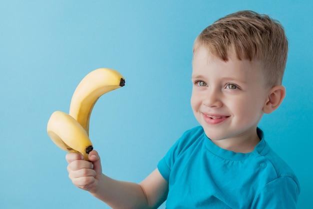小さな男の子を保持し、バナナを食べる