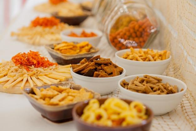 テーブルの上に塩味のスナックがたくさん、テーブルの上にスナックとチーズとクラッカーがたくさん