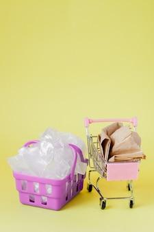 Полиэтиленовые и бумажные пакеты в корзине на желтом фоне