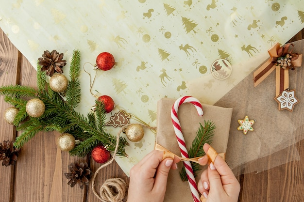 Женские руки упаковывают рождественский подарок