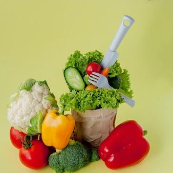 Органические овощи капуста брокколи огурцы яблоки в оберточной бумаге крафт-пакет на желтом фоне
