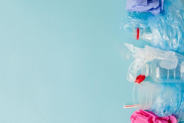 青色の背景にさまざまな種類の使い捨てのプラスチック廃棄物