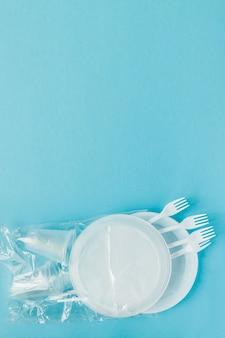 Пластиковая посуда на синем фоне. одноразовая посуда