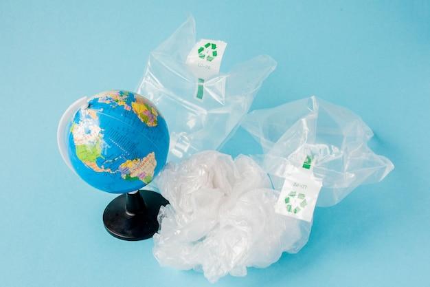 Запрет пластикового загрязнения. глобус и полиэтиленовый пакет вне земного шара