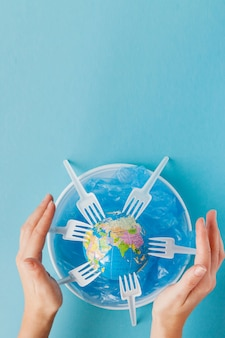 Глобус на пластиковой тарелке на синем фоне
