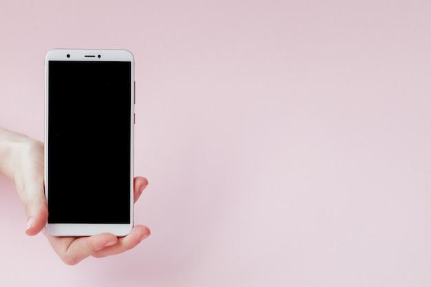 Современный мобильный телефон в руке женщины на розовом фоне