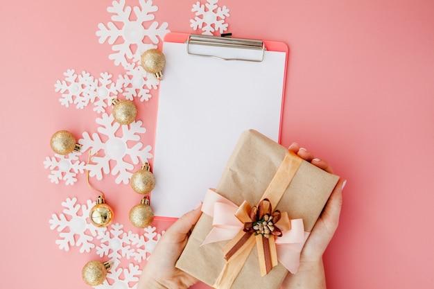 Рождественский подарок в женских руках и блокнот на розовом фоне