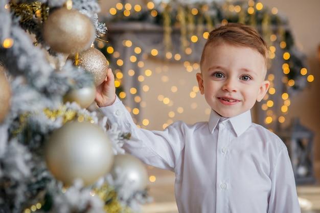 小さな男の子はクリスマスのためのクリスマスツリーを飾る