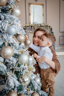 小さな男の子と母親はクリスマスのクリスマスツリーを飾る