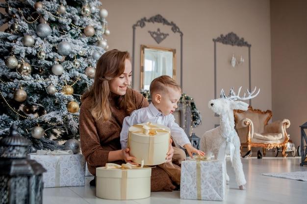 サンタの帽子でかわいい幸せな少年は、美しい部屋のインテリアで休日の朝にクリスマスプレゼントボックスを開ける