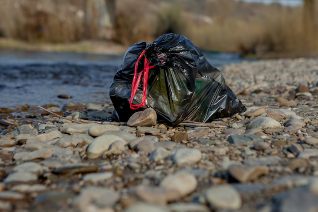 Загрязнение реки у берега, мусорный пакет у реки, пластиковые пищевые отходы, способствующие загрязнению