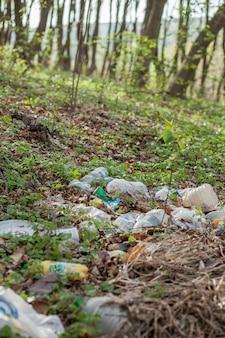 森の中のプラスチックのゴミ。隠れた自然。草の中に横たわっているプラスチック容器