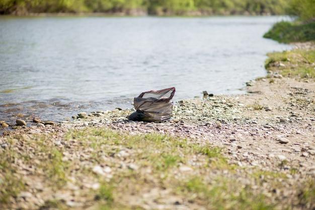 Загрязнение реки у берега, мусор у реки, пластиковые пищевые отходы, способствующие загрязнению
