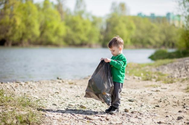 Сохраните концепцию окружающей среды, маленький мальчик собирает мусор и пластиковые бутылки на пляже, чтобы выбросить его в мусорное ведро.