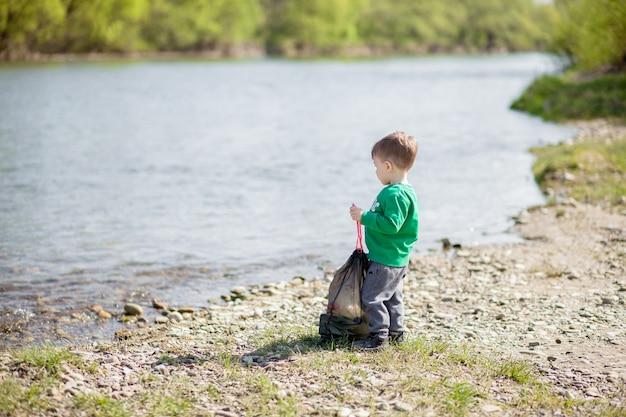 環境コンセプト、ビーチでゴミやペットボトルを収集する小さな男の子をゴミ箱に捨てる。