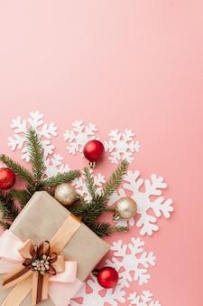 ピンクのリボンで包まれたささやかな贈り物のショットを閉じる。クリスマス。最小限。平干し。上面図