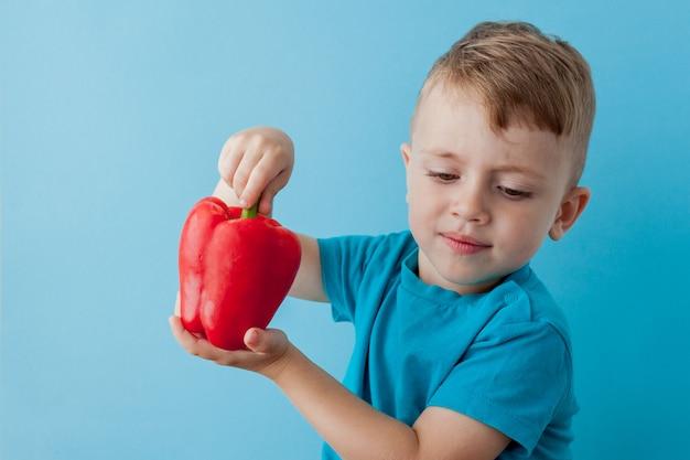 Маленький ребенок держит перец в руках. веганская и здоровая концепция