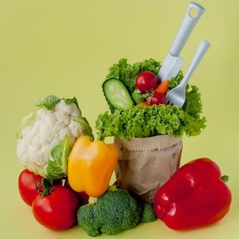 Органические овощи брокколи огурцы болгарский перец яблоки в оберточной бумаге крафт продуктовый мешок. здоровое питание, диетическое волокно веганский