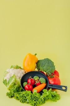 Органическая еда. здоровые овощи с брокколи, салат, красный и желтый сладкий перец, огурец на сковороде черный. вид сверху. веганские и здоровые концепции.