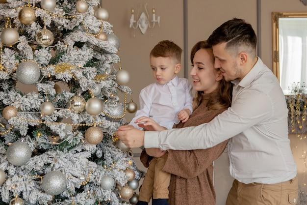 Родители и их маленький сын украшают елку игрушками и гирляндами