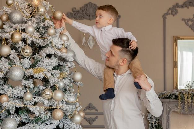 Отец и его маленький сын украшают елку игрушками и гирляндами