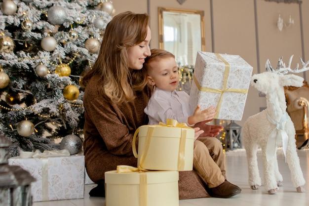 居心地の良いリビングルームでクリスマスプレゼントを開く彼女の幼い息子を持つ母。休日の家族の時間