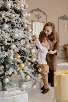 Мать и его маленький сын украшают елку игрушками и гирляндами