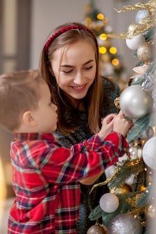 Мать и ее сын дома украшены на рождество. семейное чудо времени. веселого рождества и счастливого нового года