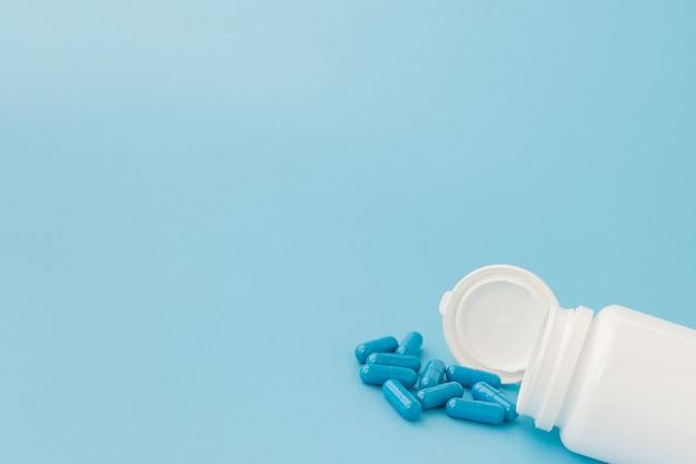 青いカプセル、青色の背景に丸薬。白い瓶にカプセル。ビタミン、女性の健康のための栄養補助食品