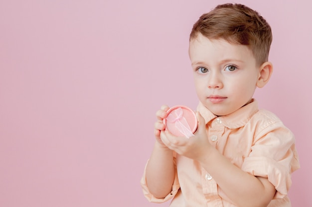 贈り物を持って幸せな小さな男の子。ピンクの背景に分離された写真。微笑む少年はプレゼントボックスを保持します。休日と誕生日の概念