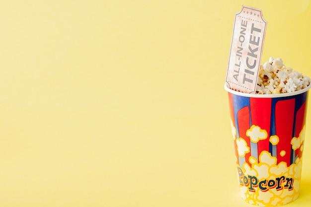 Билеты в кино и попкорн на синем фоне.